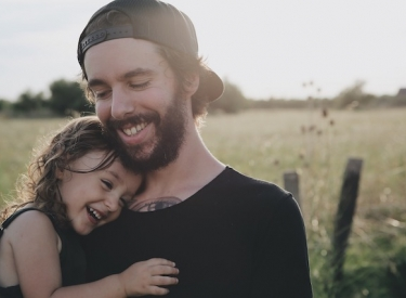 Young bearded man holding a toddler