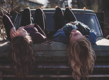 Two teen girls laying down and laughing on the hood of a truck