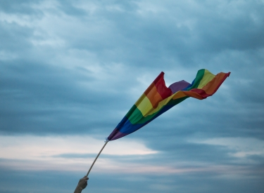A hand lifting a Pride flag toward the sky. Image courtesy of Yannis Papanastasopoulos