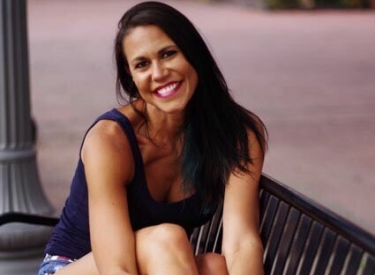 The author, Jen, sitting on a park bench, smiling