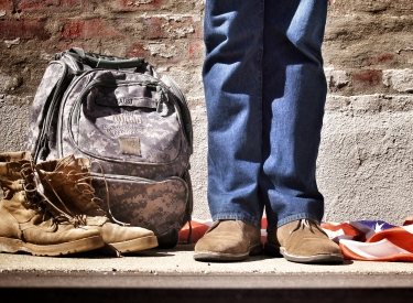 Photo by Benjamin Faust. The legs and boots of a veteran, standing next to a pair of boots, a camo backpack, and an American flag.