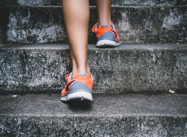 A white woman's feet, wearing orange and grey sneakers, walking up concrete stairs
