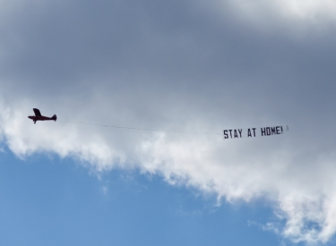 "A plane flies a ""STAY AT HOME"" banner across a cloudy sky"