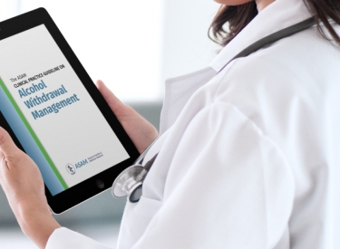 "A doctor in a white coat holds an iPad which reads ""ASAM Alcohol Withdrawal Management"""