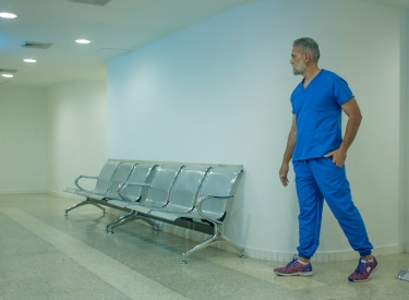 A man with a white beard wearing blue scrubs stands next to empty seats in a clinic hallway. Photo by Foto Garage AG on Unsplash