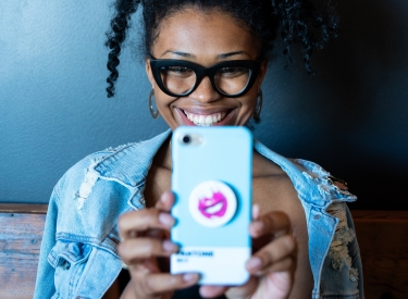 A young black woman wearing thick black glasses and a denim jacket smiles into her smartphone cameria