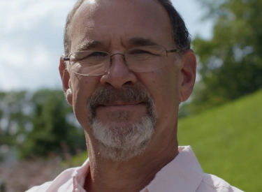 Headshot of Dr. Chudacoff: A white man with a grey beard and glasses, in a pink button down shirt, standing outside