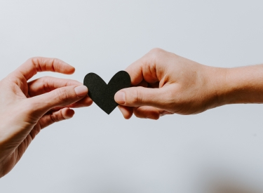 Two hands holding a cut-out of a heart. Image by Kelly Sikkema via Unsplash.