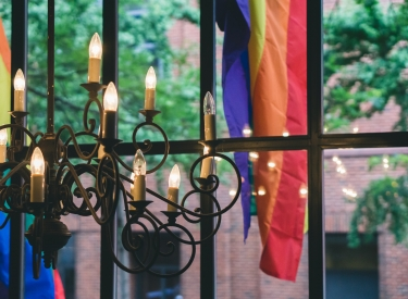 Window with candelabra and pride flag. Photo by Tatiana Rodriguez on Unsplash