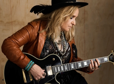 Melissa Etheridge plays guitar in a brown leather jacket and wide-brimmed black hat
