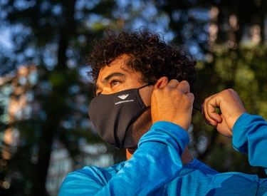 A young man with curly hair in a blue long sleeved tee puts on his face mask