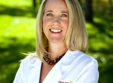 Headshot of Dr. Lisa Hunsicker, a blonde woman in a white lab coat standing outside