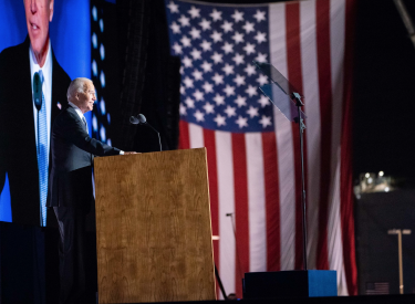 President Joe Biden giving a speech at a podium, with a large monitor and American flag in the background. Photo by Adam Schultz.