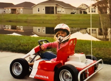 A childhood photo of the author's daughter, smiling in a red and white go cart