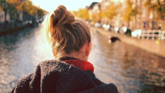 A girl in a coat looks out at a river