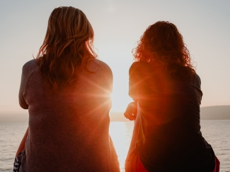 Two women watch the sunset on a beach