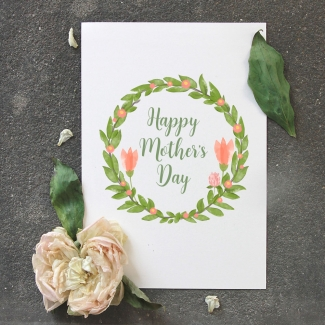 "A white card surrounded by flowers and leaves with an inscription of ""Happy Mother's Day."" The text is in green calligraphy, surrounded by a green wreath with red tulips."