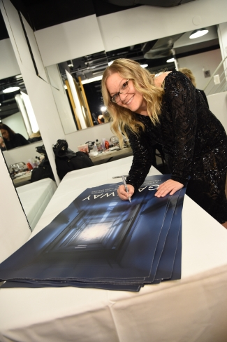 Jen Wysong, wearing a sparkly black dress, signing a movie poster