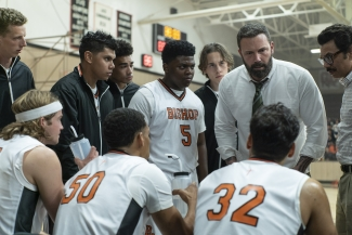 Ben Affleck as Jack, wearing a shirt and tie, talking to a group of young basketball players