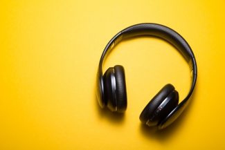 Black headphones on a yellow background. Photo by Malte Wingen on Unsplash