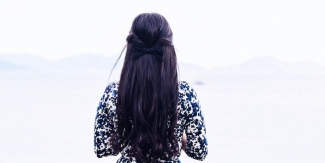 Photo by Suhyeon Choi on Unsplash. Woman in a patterned dress with long dark hair looks out at the sea.