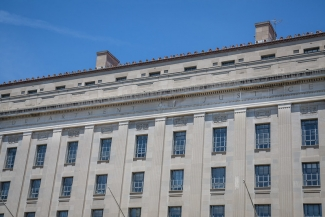 The United States Department of Justice, a large grey stone building against a blue sky. Photo by Tony Webster