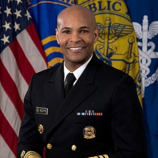 U.S. Surgeon General Jerome Adams stands in uniform in front of flags.